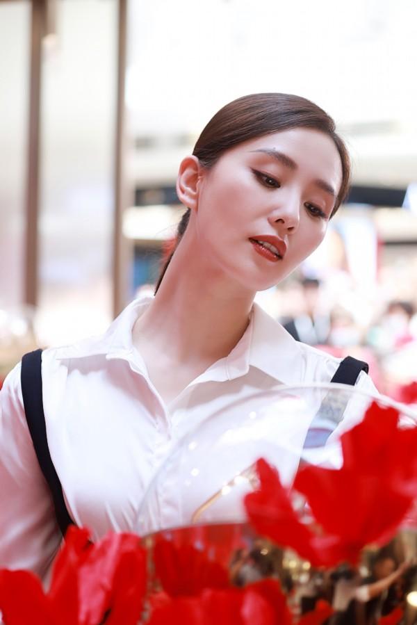 刘诗诗歪头赏花秀天鹅颈 穿白衬衫梳低马尾气质如兰